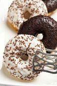 Black and white chocolate sprinkle donuts with pastry tong closeup