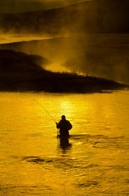 foto of fly rod  - Man fishing in river with fly rod and waders - JPG