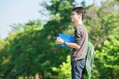 Asian Student Holding Books And Smiling While Standing In Park At College