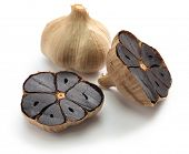 black garlic bulbs and cloves on white background