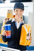 Portrait of smiling female worker holding popcorn and drink at cinema concession stand