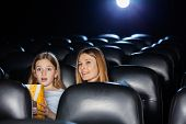 Amazed mother and daughter watching movie in cinema theater