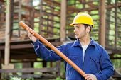 Young male worker examining pipe against incomplete timber cabin at construction site