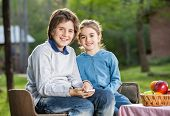 Portrait of happy siblings with smartphone at campsite