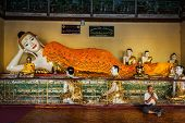 YANGON, MYANMAR - JANUARY 3, 2014: Man meditating near statue of Recumbent Buddha in Shwedagon Paya pagoda