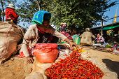 INLE LAKE, MYANMAR - JANUARY 7, 2014: Woman selling hot red chilli pepper in rural market