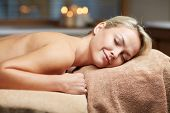 people, beauty, spa, healthy lifestyle and relaxation concept - beautiful young woman lying on massage table in spa