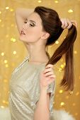 Beautiful young woman with long hair on bright background