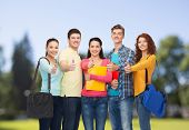 friendship, vacation, education, gesture and people concept - group of smiling teenagers with folders and school bags showing thumbs up over park background
