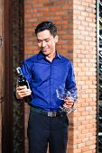 Asian man holding bottle of wine and wine glasses