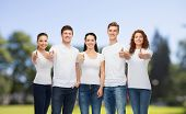 advertising, nature, summer holidays and people concept - group of smiling teenagers in white blank t-shirts showing thumbs up