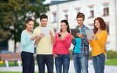 friendship, technology, education, school and people concept - group of smiling teenagers with smartphones and tablet pc computers over campus background