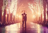 image of single man  - Couple with umbrella kissing at night alley - JPG