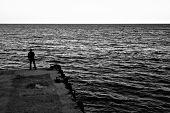 Evening. Jetty. Fisherman