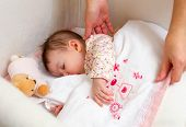 foto of caress  - Hands of mother caressing her cute baby girl sleeping in a cot with pacifier and stuffed toy - JPG