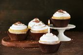 Delicious cupcakes with candle on table on brown background