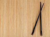 Pair of chopsticks on light bamboo mat background