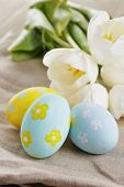 handpainted easter eggs and white tulips on wood table