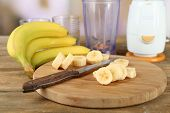 Sliced banana on cutting board, on wooden table, on bright background