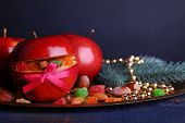 Red apples stuffed with dried fruits on metal tray on color wooden table and dark background