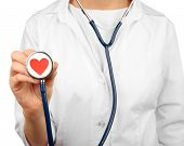 Stethoscope with heart in doctor hands, close-up