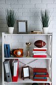 Bookshelves with books and decorative objects on brick wall background