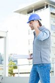 Side view of male architect with blueprints using mobile phone outside building