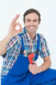 Portrait of plumber holding monkey wrench while gesturing OK sign over white background