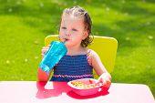 Toddler kid girl drinking eating macaroni pasta in garden turf grass outdoor
