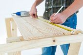 Cropped image of carpenter marking with measure tape on wooden plank against white background