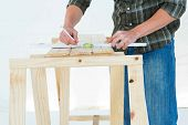 Cropped image of worker using spirit level to mark on wooden plank against white background