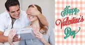 Man covering the eyes of his girlfriend while giving her a present against happy valentines day