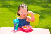 Toddler kid girl eating macaroni tomato pasta in garden turf grass