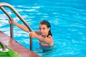 Kid girl in swimming pool at summer vacation posing looking camera