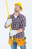 Repairman wearing tool belt while examining spirit level on white background