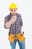 Portrait of confident male repairman pointing at you on white background