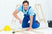 Portrait of happy repairman fixing screw on plank over white background