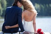 foto of heterosexual couple  - Beautiful couple relaxing on a foot bridge near a lake acting very romantic - JPG