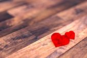 Two red hearts on the wood floor