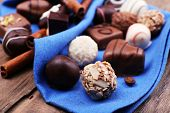 Group of chocolates with cinnamon stick on blue napkin and wooden background
