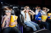 Scared girl screaming while watching 3D movie with siblings in cinema theater