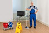 foto of janitor  - Male Janitor With Mop And Cleaning Equipments Gesturing Thumbs Up Sign - JPG