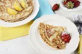 Shrove Pancake Tuesday Pancakes With Lemons And Strawberries With Yellow And Blue Napkins On White V