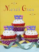 Mardi Gras Cupcakes With Purple Mask Toppers On Rustic Style Vintage Yellow And Aqua Blue Wood Bakcg