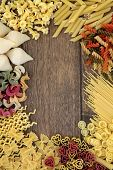 Italian pasta food selection forming an abstract border over old oak background.