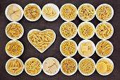 picture of pasta  - Large pasta food selection in round bowls and in a heart shaped bowl over brown background - JPG