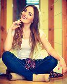 Girl In Denim Trousers Sitting On Floor