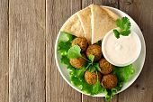 stock photo of pita  - Plate of falafel with pita bread and tzatziki sauce on wooden table - JPG