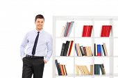 Young businessman leaning on a bookshelf isolated on white background