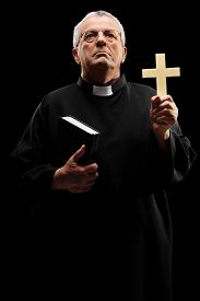 stock photo of priest  - Vertical shot of a mature priest holding a cross and looking up on black background - JPG